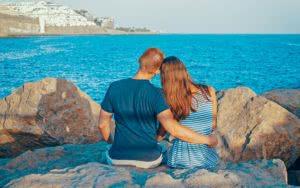 αγόρι και κορίτσι κάθονται σε παραλία