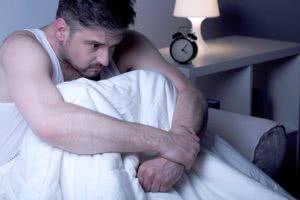 άνδρας κάθεται προβληματισμένος στο κρεββάτι