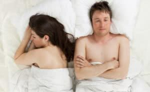 ζευγάρι σε κρεβάτι με προβληματισμένο άνδρα