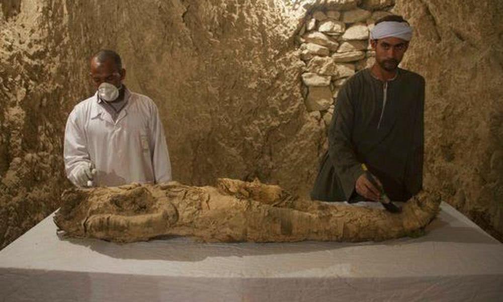 μούμια και αρχαιολόγοι που την καθαρίζουν